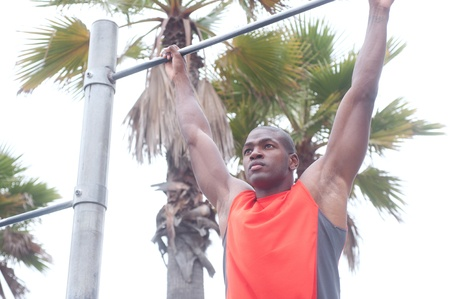 pullups: portrait of an African American athlete doing pullups outdoors