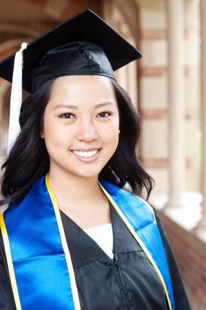 portrait of a beautiful young asian woman in graduation cap and gown standing outside on campus