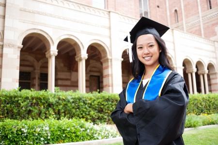 Porträt einer schönen jungen asiatischen Frau in Graduierung Mütze und Mantel steht draußen auf dem Campus Standard-Bild - 14136160