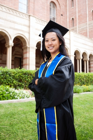 higher learning: portrait of a beautiful young asian woman in graduation cap and gown standing outside on campus