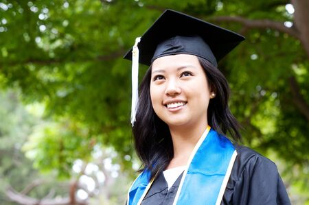 portrait of a beautiful young asian woman in graduation cap and gown standing outside on campus photo