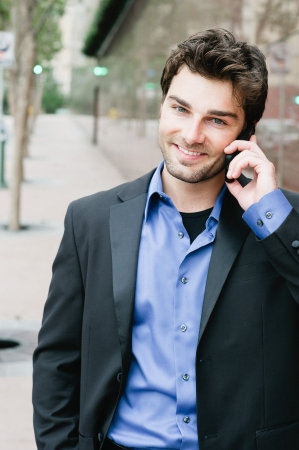Portret van een jonge zakenman op de telefoon die buiten het kantoor Stockfoto