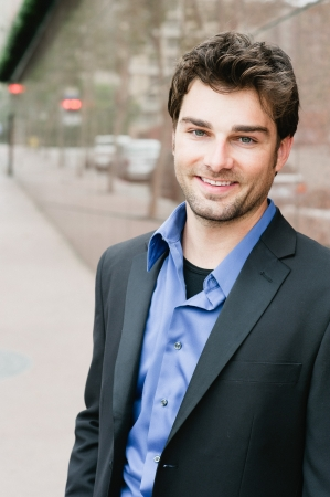 Portrait of a happy young businessman in suit standing outside office Stock Photo