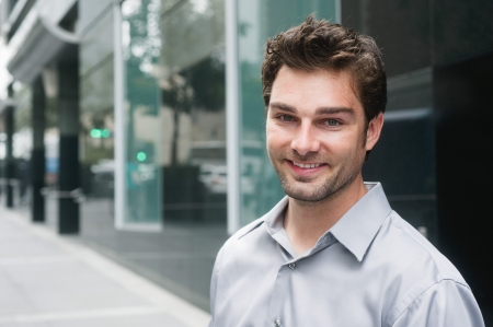 Portrait of a happy young businessman in suit standing outside office Standard-Bild