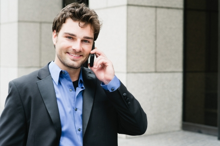 Portrait of a young businessman on the phone standing outside the office photo