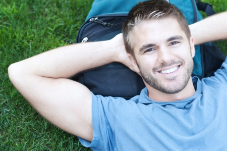 portrait of a college student lying in grass on campus Stock Photo