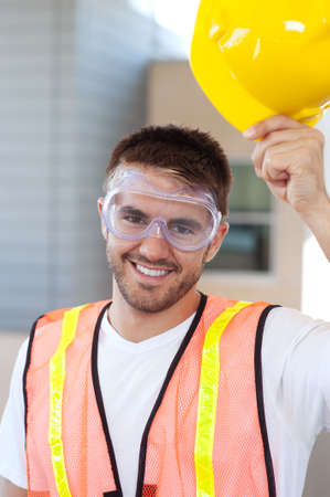 safety goggles: portrait of a happy construction worker shot outside