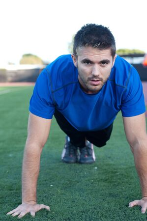 Handsome, young athlete doing push ups on an athletic field photo