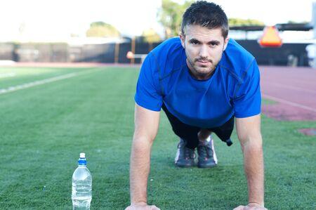 Knappe, jonge atleet doen push-ups op een sportveld