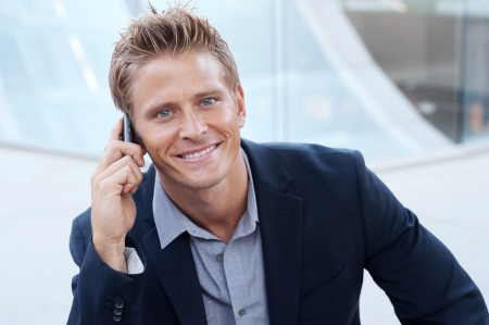 Closeup portrait of handsome business man using cell phone, smiling photo