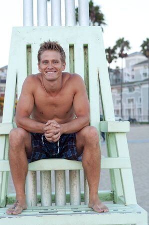 portrait of a young, fit, handsome lifeguard on the beach photo