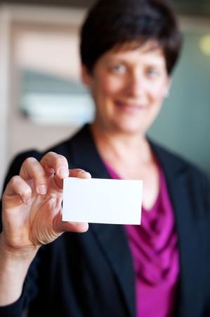 businesscard: portrait of a pretty, mature businesswoman holding a businesscard