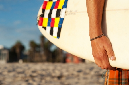 closeup shot of a surfer holding a surfboard at the beach Stock Photo