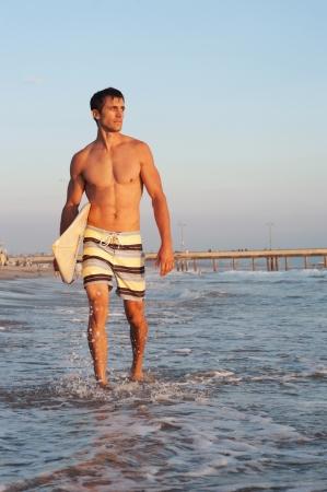 ni�o sin camisa: Retrato de un surfista en la playa con tabla de surf