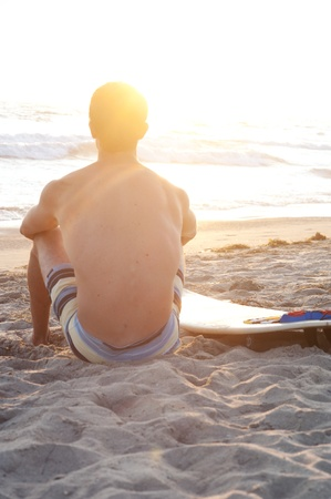 good looking boy: surfer sitting on the beach during sunset Stock Photo