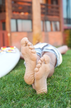 foot model: closeup of feet of a surfer lying in the grass