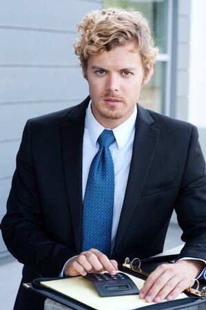 portrait of a young businessman standing outside office photo