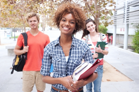 Happy group of students holding notebooks outdoors Stock Photo