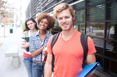 Happy group of students holding notebooks outdoors Stock Photo - 15413486