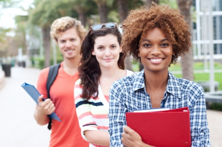Happy group of students holding notebooks outdoors Standard-Bild