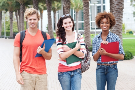 sociable: Happy group of students holding notebooks outdoors Stock Photo