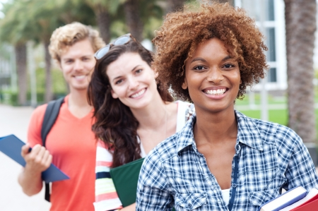 college campus: Happy group of students holding notebooks outdoors Stock Photo