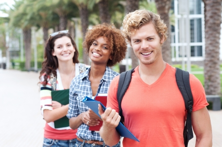 uni: Happy group of students holding notebooks outdoors Stock Photo