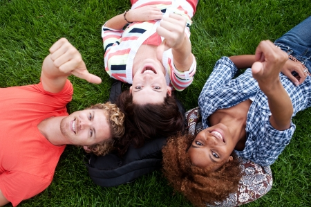 group of happy college students lying in the grass looking up photo