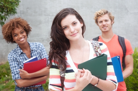 Happy group of students holding notebooks outdoors photo