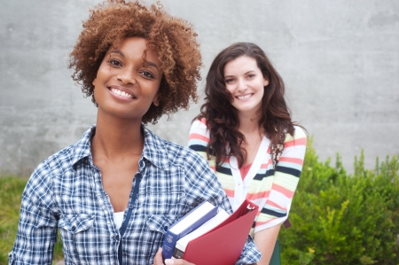 Happy pair of students holding notebooks outdoors