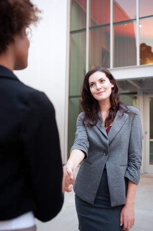 Attractive woman business team shaking hands at office photo