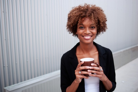 portrait of a pretty African American executive holding a mug photo