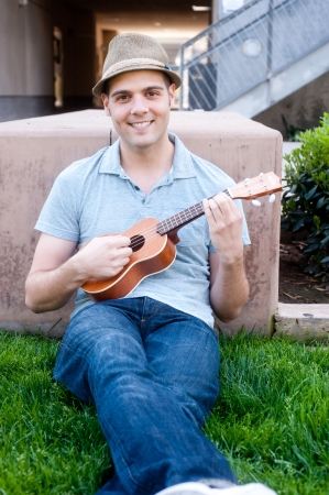 happy young male student on campus with ukulele