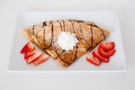 Crepe mit frischen Erdbeeren mit Zucker bestreut auf einem weißen Teller Standard-Bild - 21592466