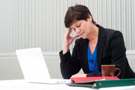 businesswoman under stress, fatigue, and headache at office