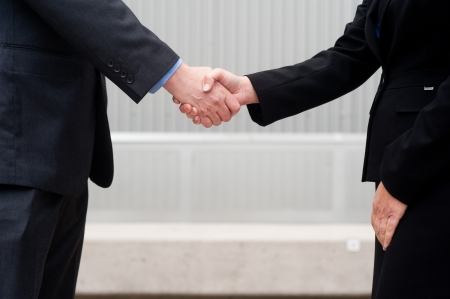 client meeting: closeup handshake isolated on business background