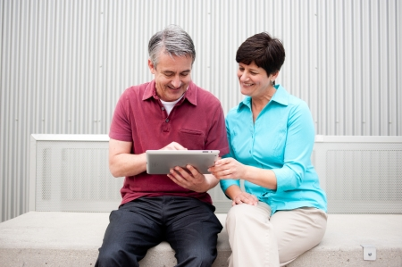 elderly couple sitting, on the tablet computer photo