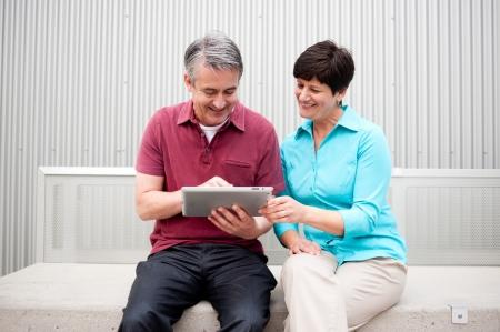 LTeres Ehepaar sitzt auf dem Tablet-Computer Standard-Bild - 21876444