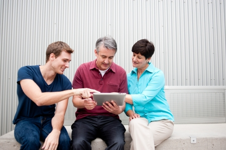 communicative: family having fun on tablet Stock Photo
