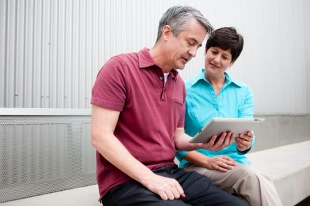 LTeres Ehepaar sitzt auf dem Tablet-Computer Standard-Bild - 21876445