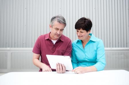 LTeres Ehepaar sitzt auf dem Tablet-Computer Standard-Bild - 21876446