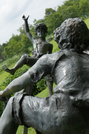 Child brass statue  playing in the park Stock Photo