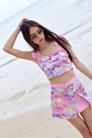 expressed: Asian woman standing on a beach in Thailand . Thailand has expressed Happy to be a model.
