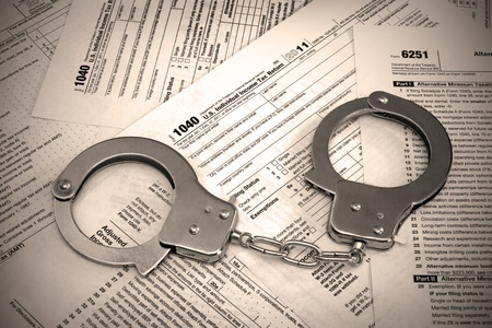 Tax papers and handcuffs