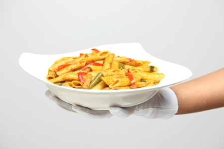 A person holding a bowl of pasta with pepper sauce