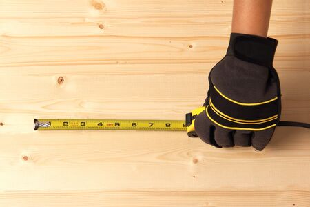 Worker taking measurement on a block of wood Stock Photo
