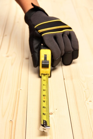 A worker measuring a block of wood using a measuring tool Stock Photo