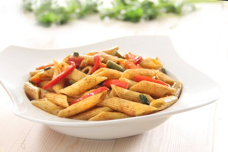 Penne pasta cooked with spicy pepper sauce with vegables Stock Photo