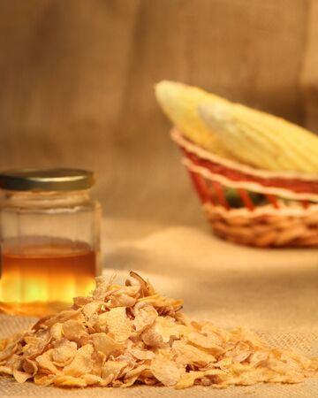Cornflakes with honey and corn cobs in a basket
