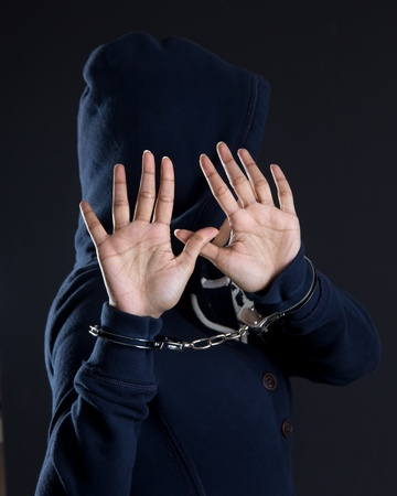 Women in handcuffs avoiding being photographed
